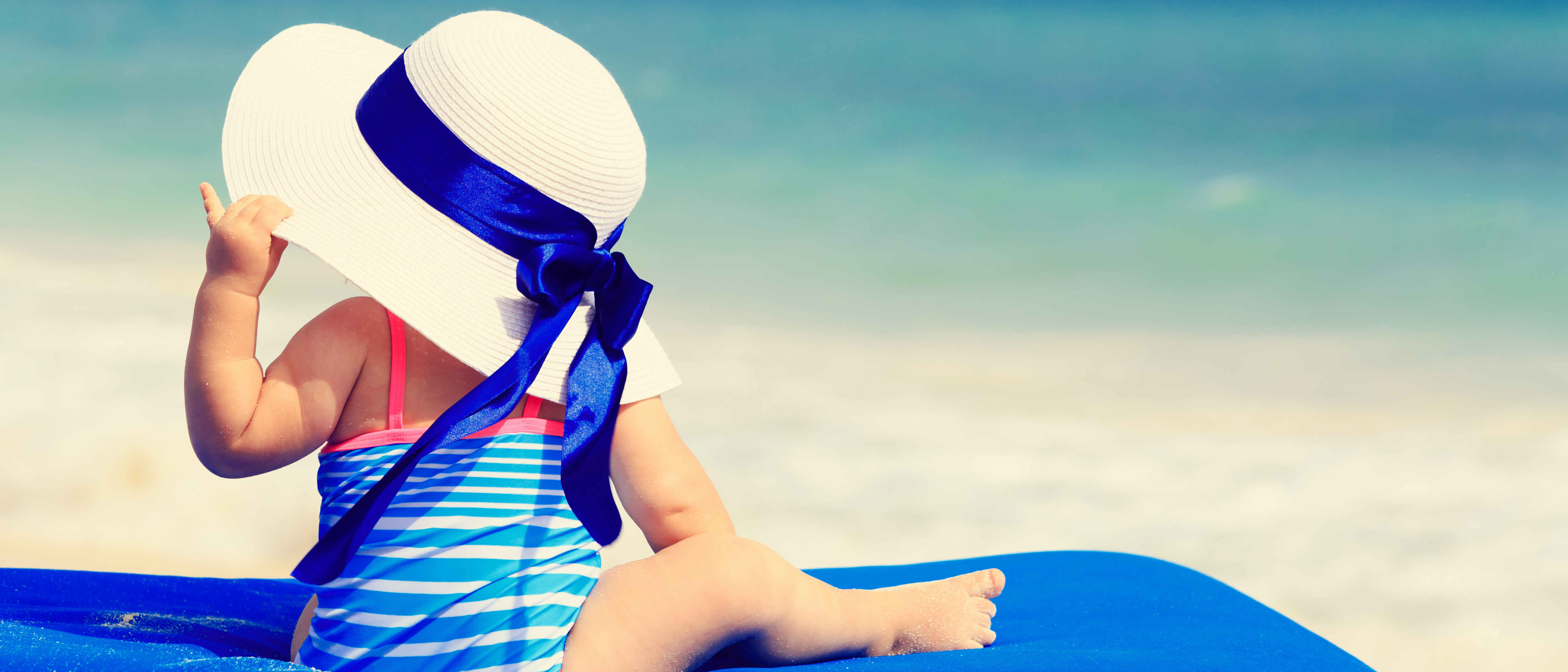 little girl in big hat on summer tropical beach