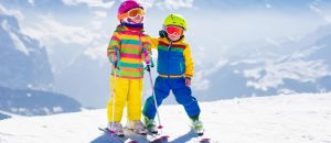 Kids skiing in mountains. Active children with safety helmet, goggles and poles. Ski race for young kids. Winter sport for family. Child ski lesson in alpine school. Little skier racing in snow